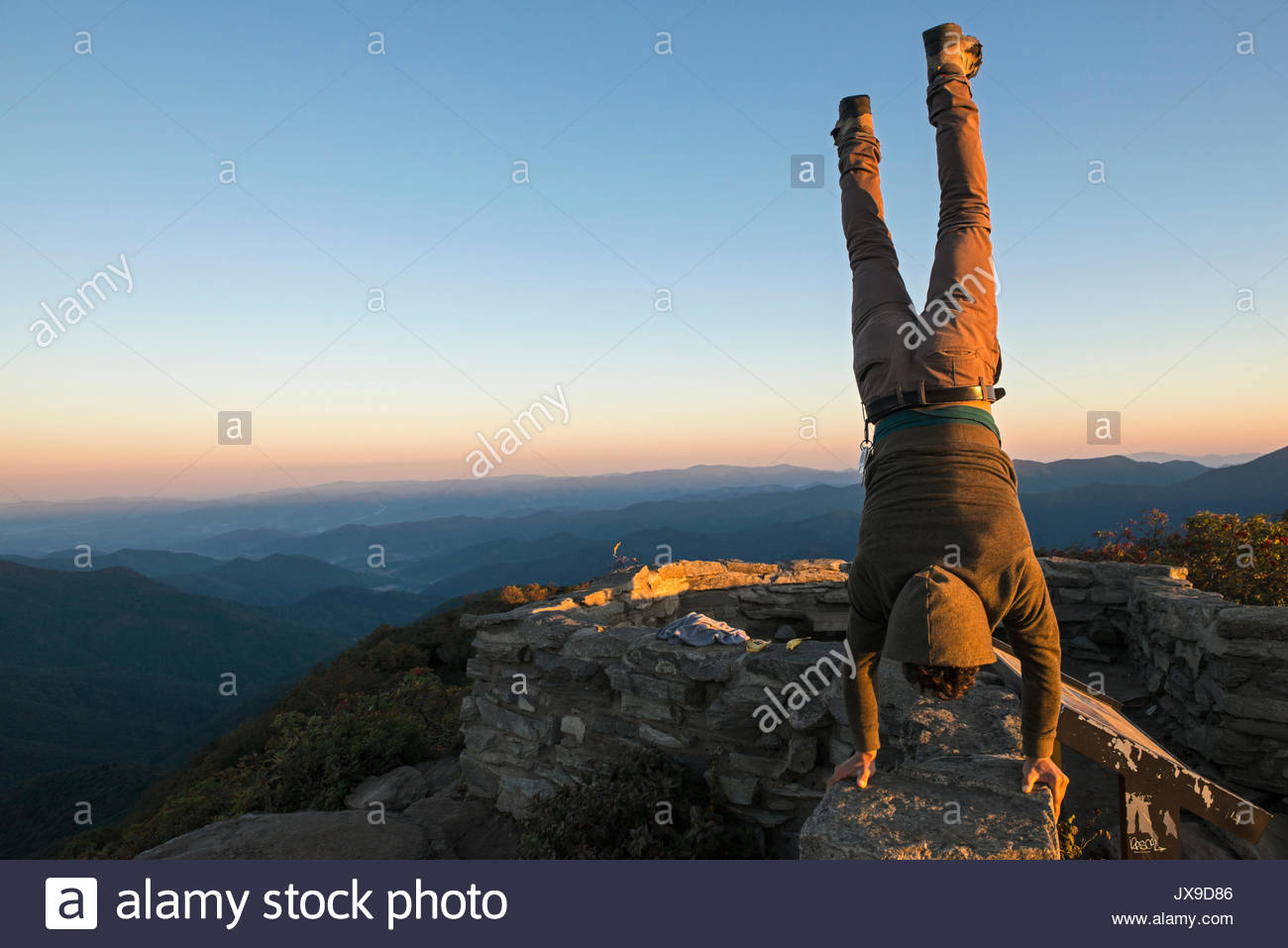 A man performs a handstand at the top of Craggy Pinnacle Trail along the Blue Ridge Parkway. - Stock Image