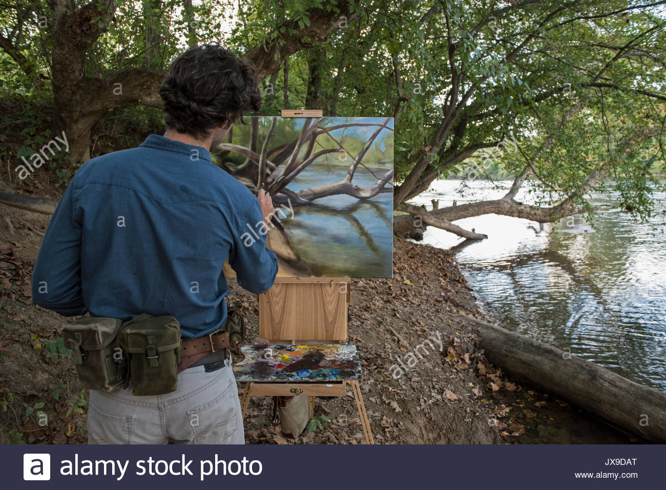 A self-trained painter who lives working on a plein air painting along the banks of the French Broad River. - Stock Image