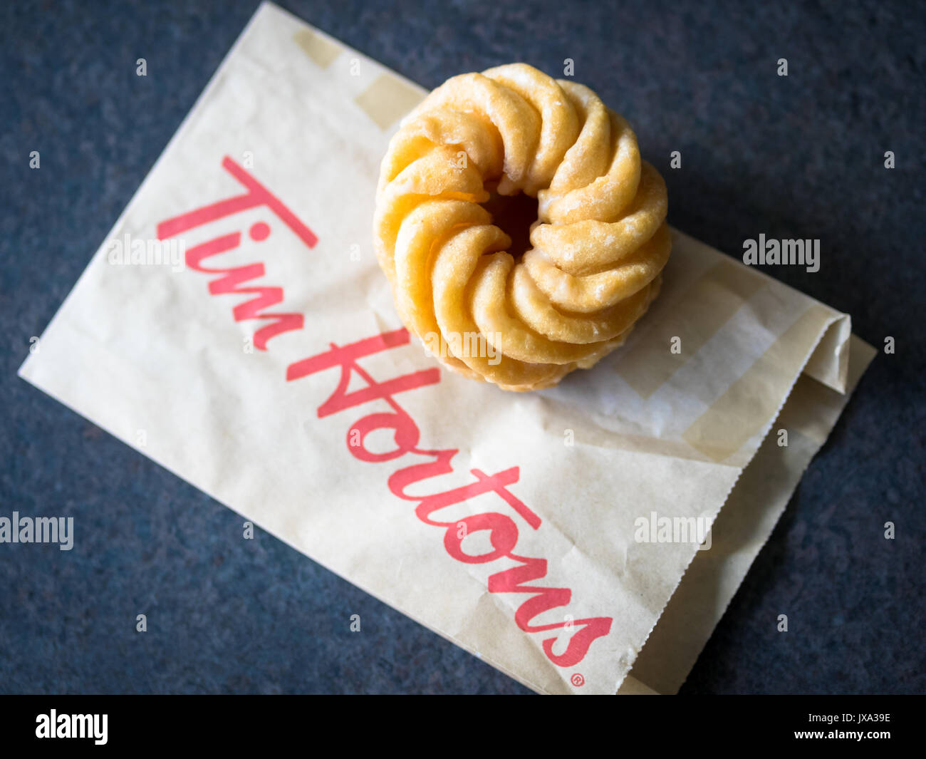 A honey cruller donut from Tim Hortons, a popular Canadian fast food restaurant and donut shop. - Stock Image
