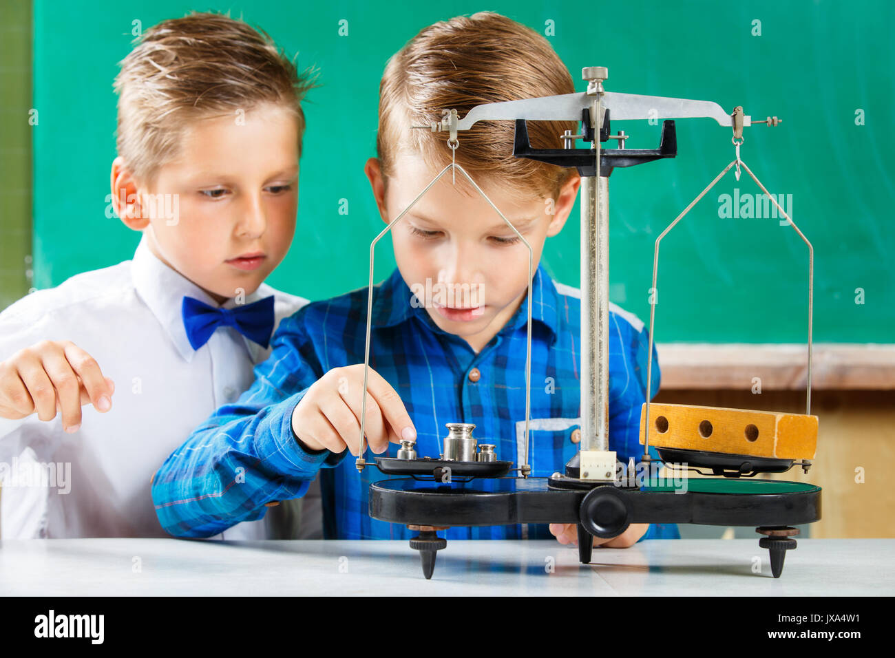 Two small schoolmates use scales on lesson in school - Stock Image