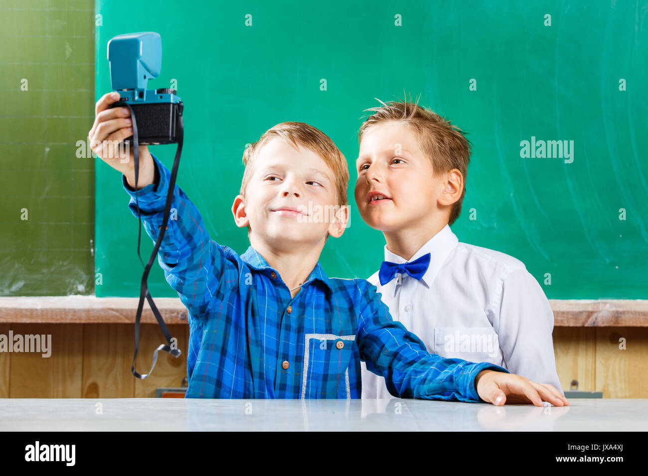 Two schoolmates make selfie at blackboard in school. Back to school concept background - Stock Image