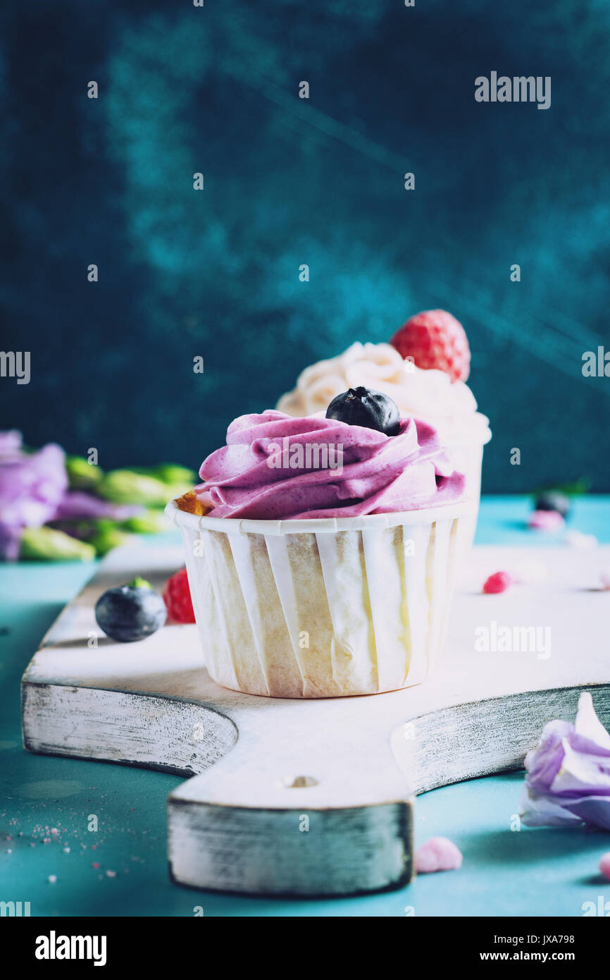 Colorful cupcakes with buttercream on cutting board. Closeup view, toned image - Stock Image