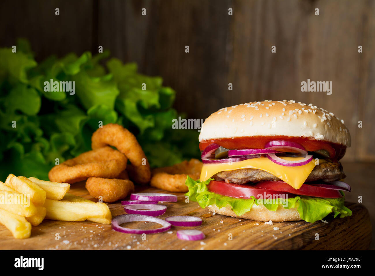 Cheeseburger, french fries and onion rings on wooden cutting board over wooden background. Closeup view, selective focus. Fast food concept - Stock Image