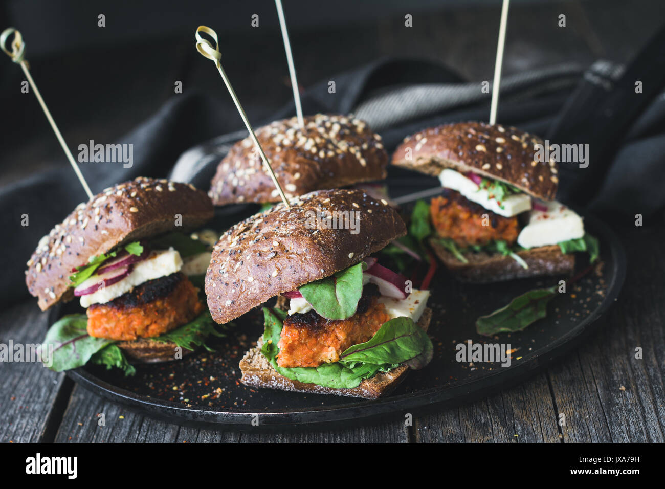 Vegetarian tofu carrot burger sliders served on iron skillet. Closeup view, toned image - Stock Image