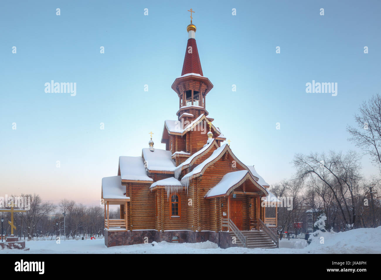 Wooden orthodox christian temple exterior in winter in forest. Stock Photo