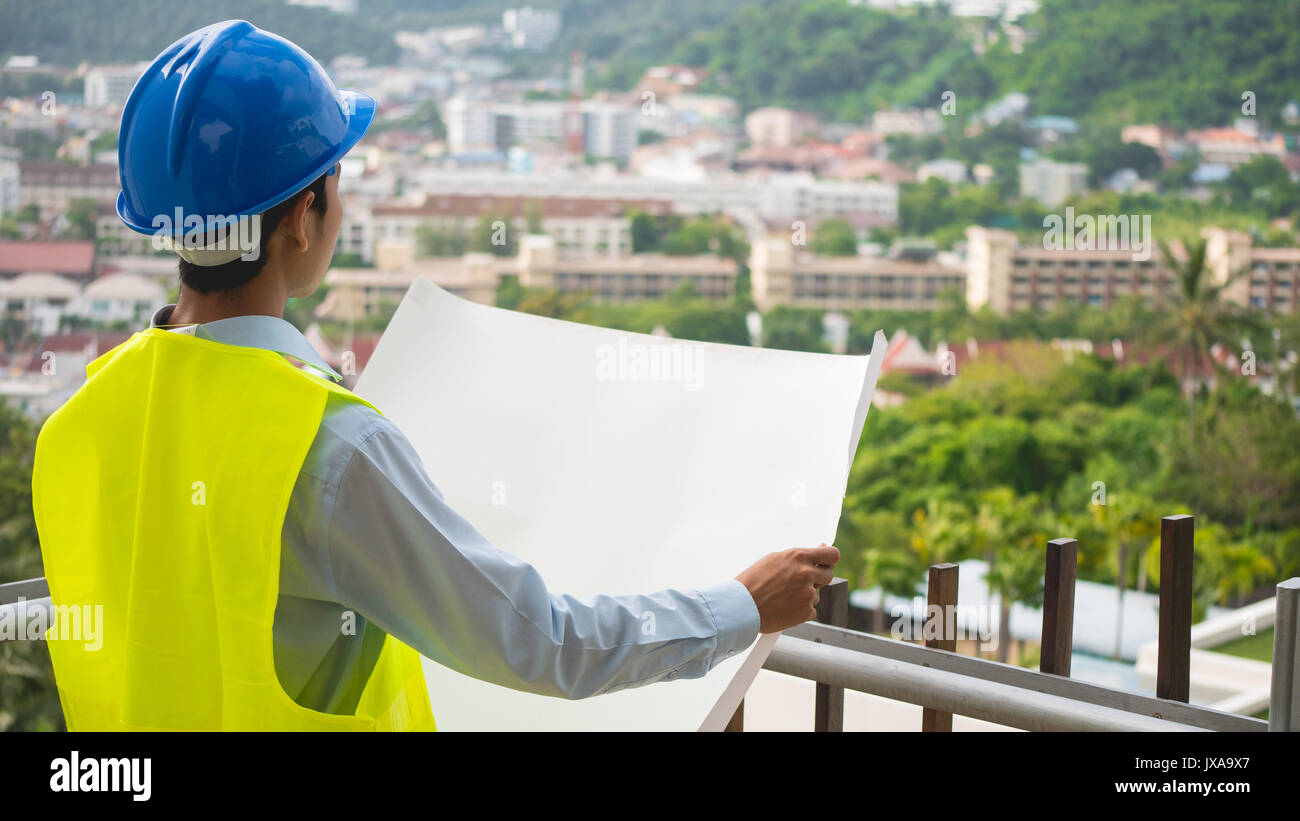 A construction engineer. Wearing a helmet and vest holding a plans with blur city or building background in construction Stock Photo