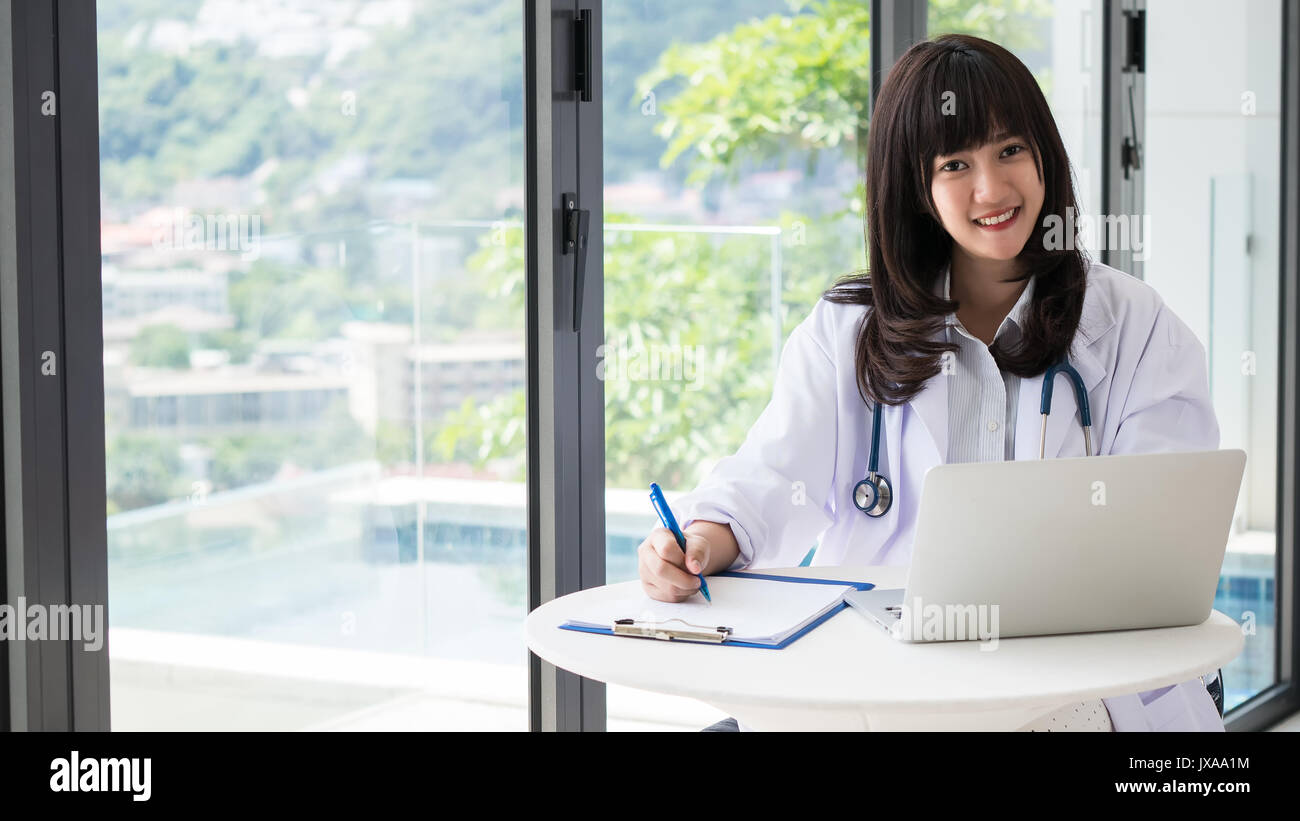Young asia doctor are Smiling and writing a report for a treatment plan with Stethoscope,The hand holding the pen and find information with laptops in - Stock Image