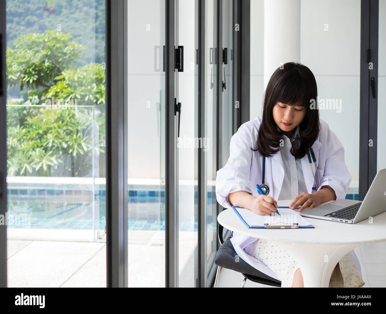 Young asia doctor is writing a report for a treatment plan with Stethoscope,The hand holding the pen and find information with laptops in health care  - Stock Image