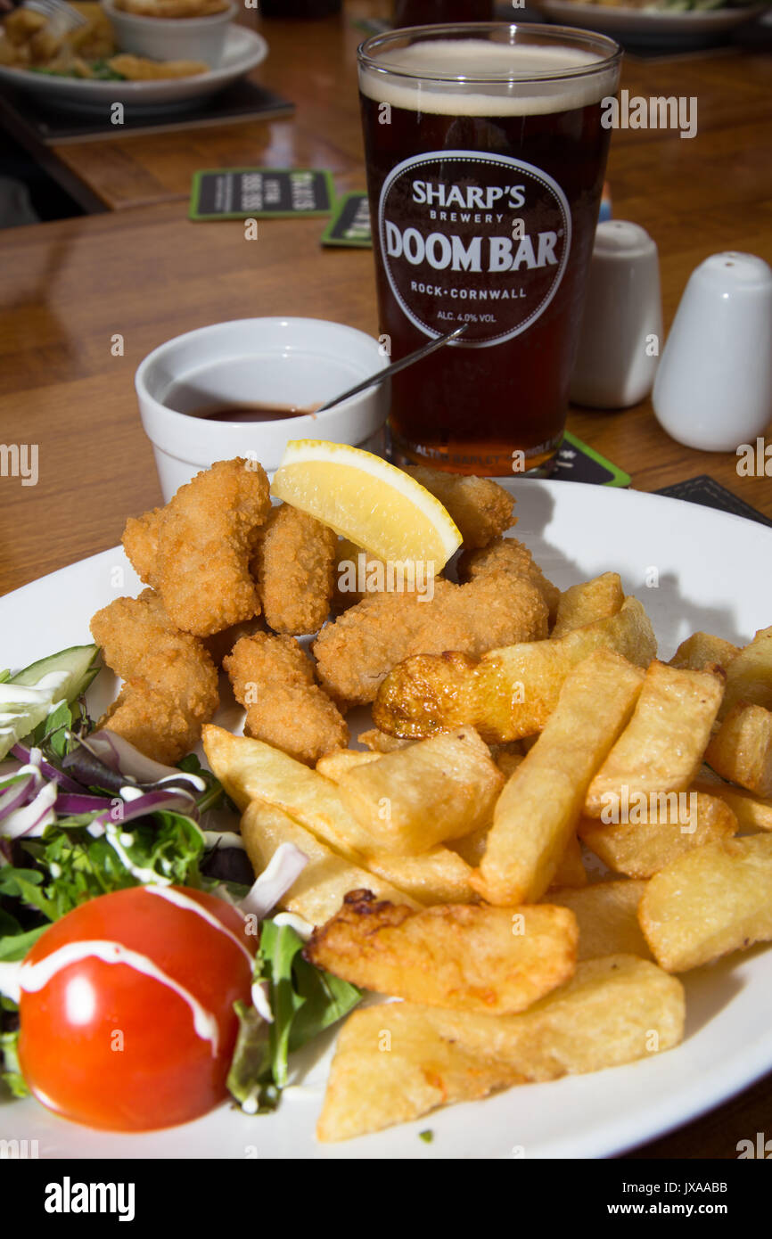An English pub/bar/restaurant lunch of traditional Breaded fried Scampi with chips/fries, side salad and a pint of ale/beer. - Stock Image