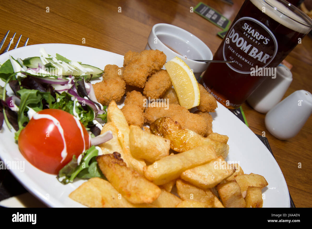 An English pub/bar/restaurant lunch of traditional Breaded fried Scampi with chips/fries, side salad and a pint Stock Photo