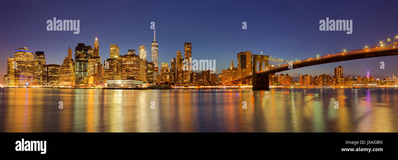 The New York City skyline and the Brooklyn Bridge photographed at night. - Stock Image