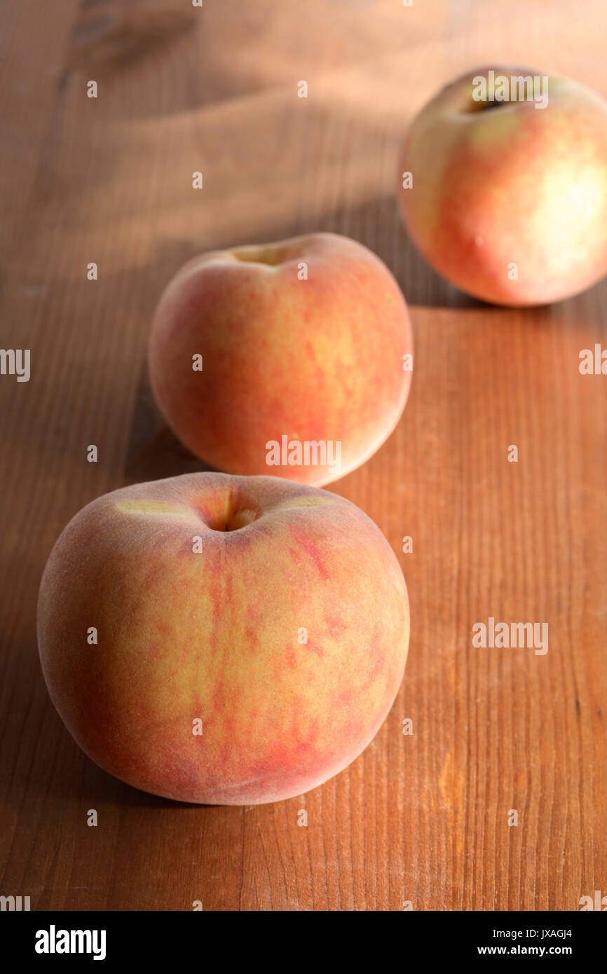 Three freshness peach fruits lying on wooden surface Stock Photo