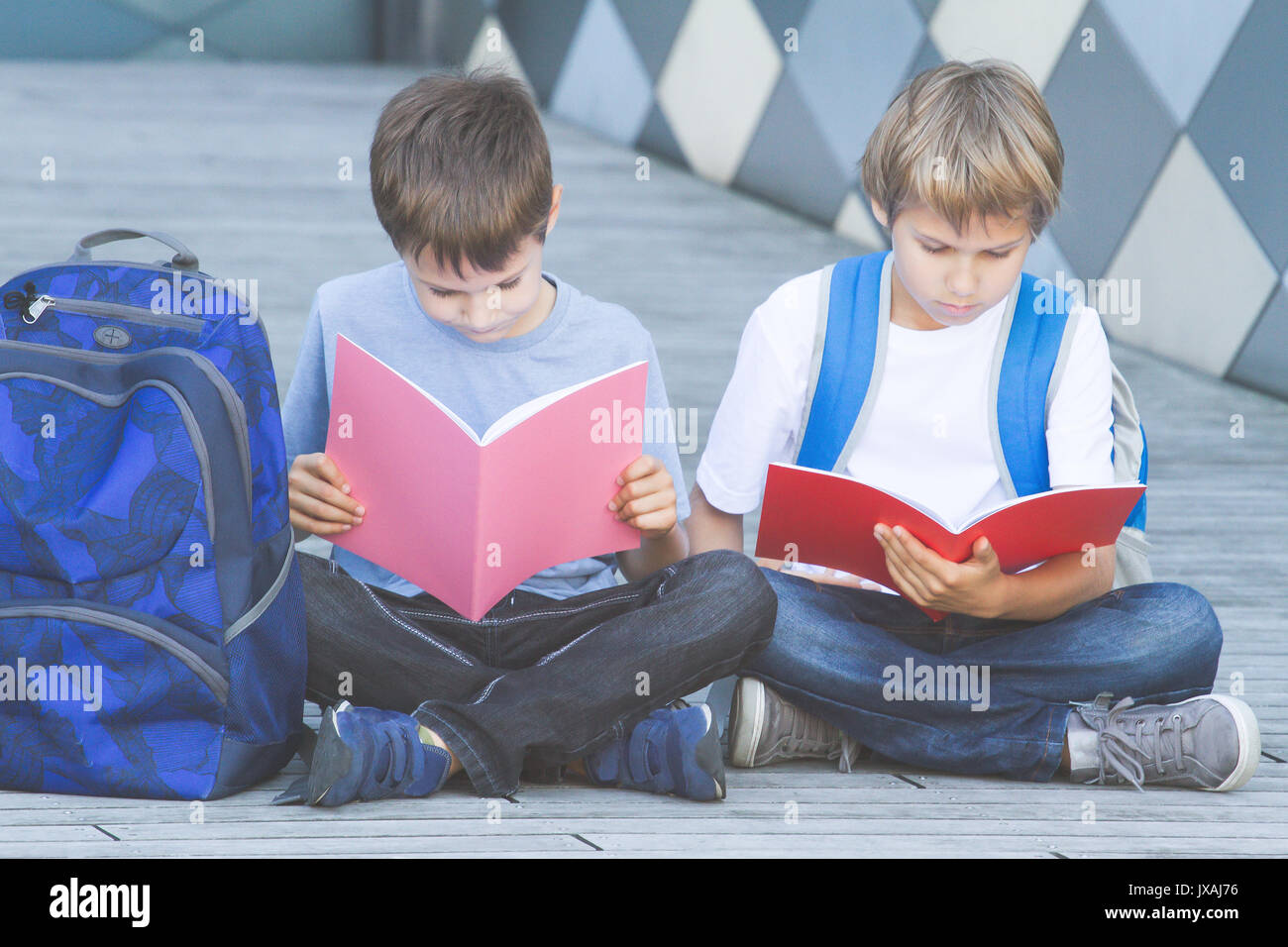 Schoolboys reading books. Kids doing homework outdoors. Back to school concept. Stock Photo
