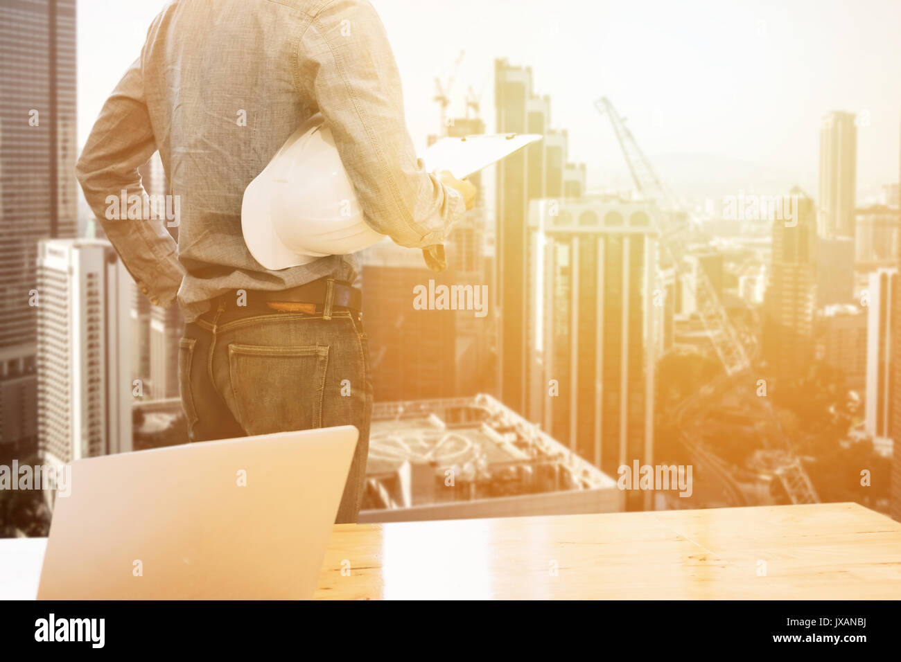 Builder engineer holding security helmet look at blueprint paper builder engineer holding security helmet look at blueprint paper construction drawing plan and laptop computer malvernweather Image collections