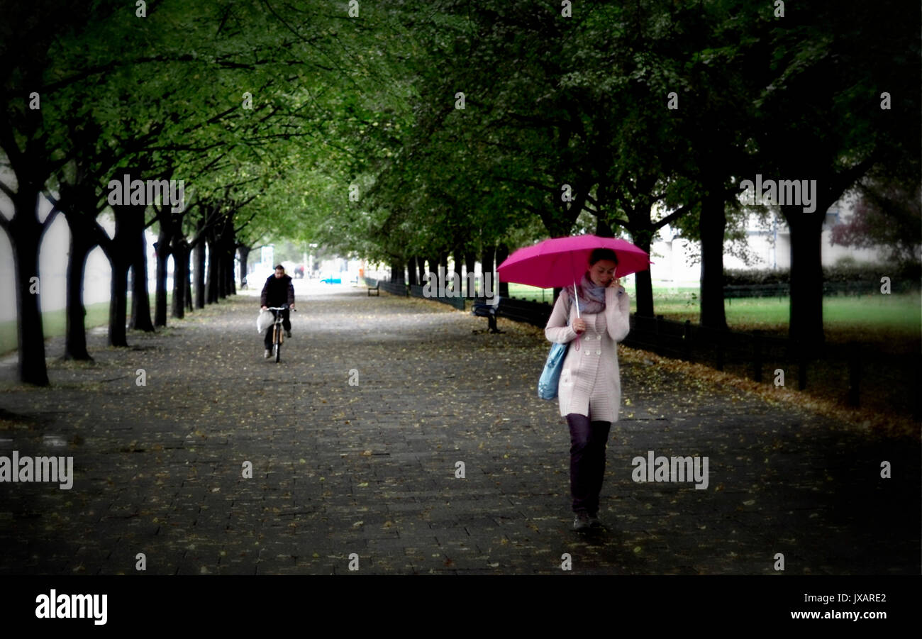 BERLIN - WOMAN WITH PINK UMBRELLA - BERLIN WOMAN - AUTUMN IN BERLIN -RAIN IN BERLIN- AUTUMN SEASON - BERLIN GERMANY© Stock Photo