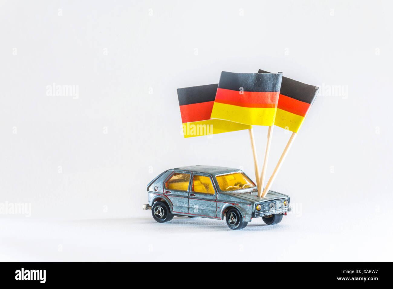 Modellauto. Ein Spielzeugauto der Marke Volkswagen VW Golf, leicht demoliert. Mit Deutschlandflagge, Made in Germany. - Stock Image