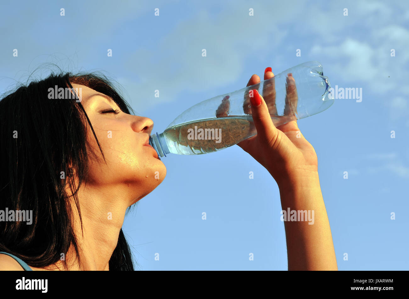 Thirst.Thirsty girl drinks cold water in hot day - Stock Image