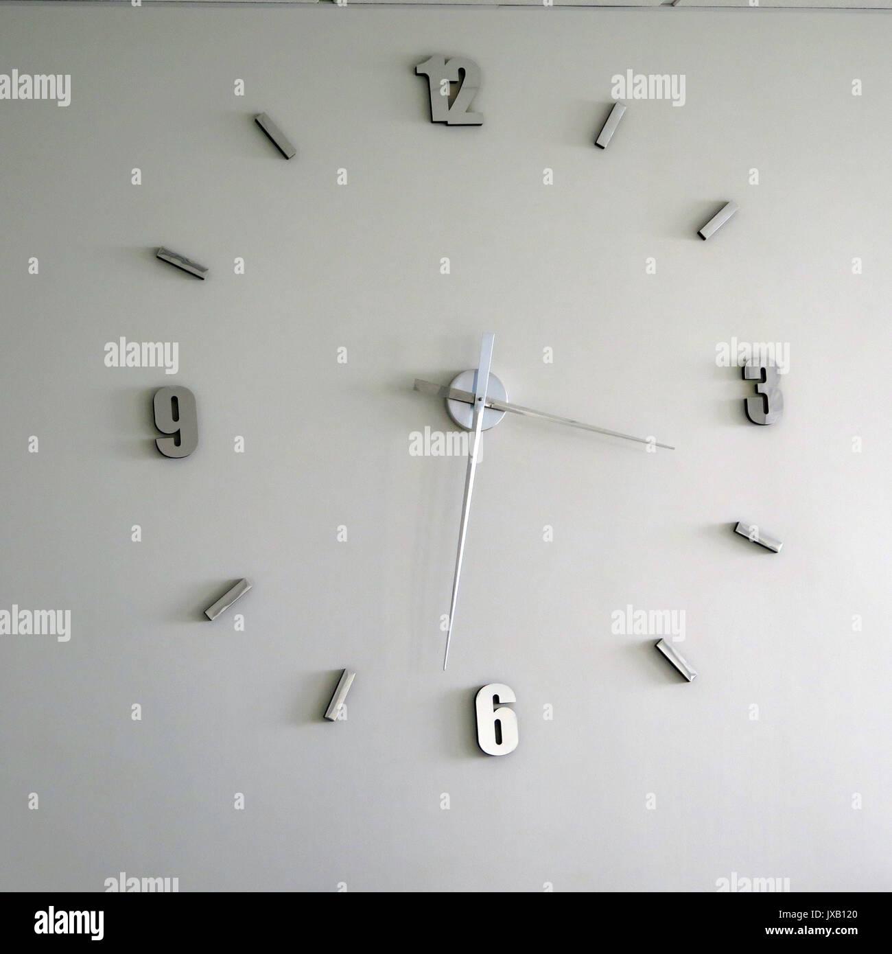 Large stylish wall clock in Weymouth restaurant - Stock Image