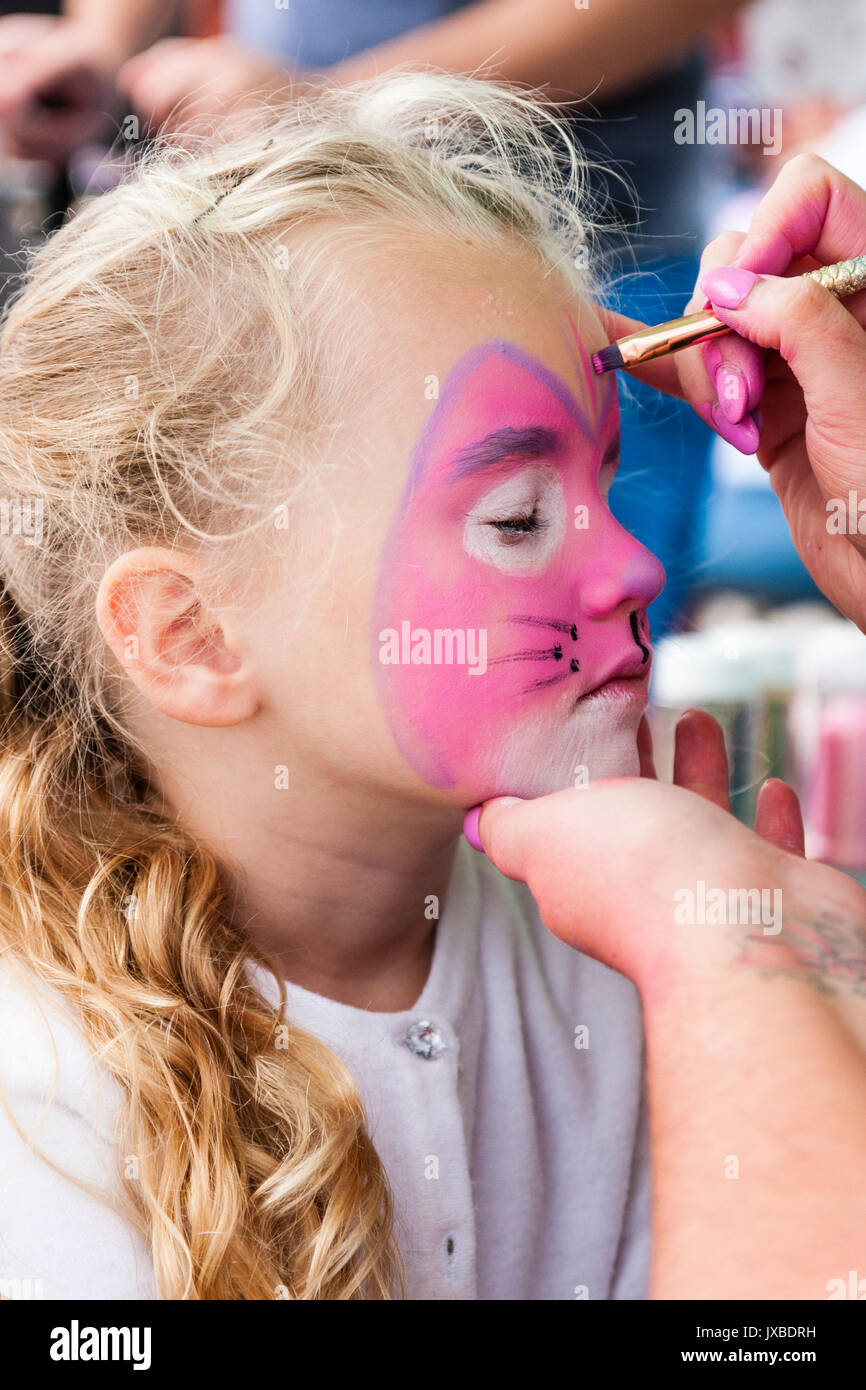Caucasian blonde child, girl, 7-8 years old, side view, having face painted pink with cat face. Hand holding her chin, another hand holding brush. - Stock Image