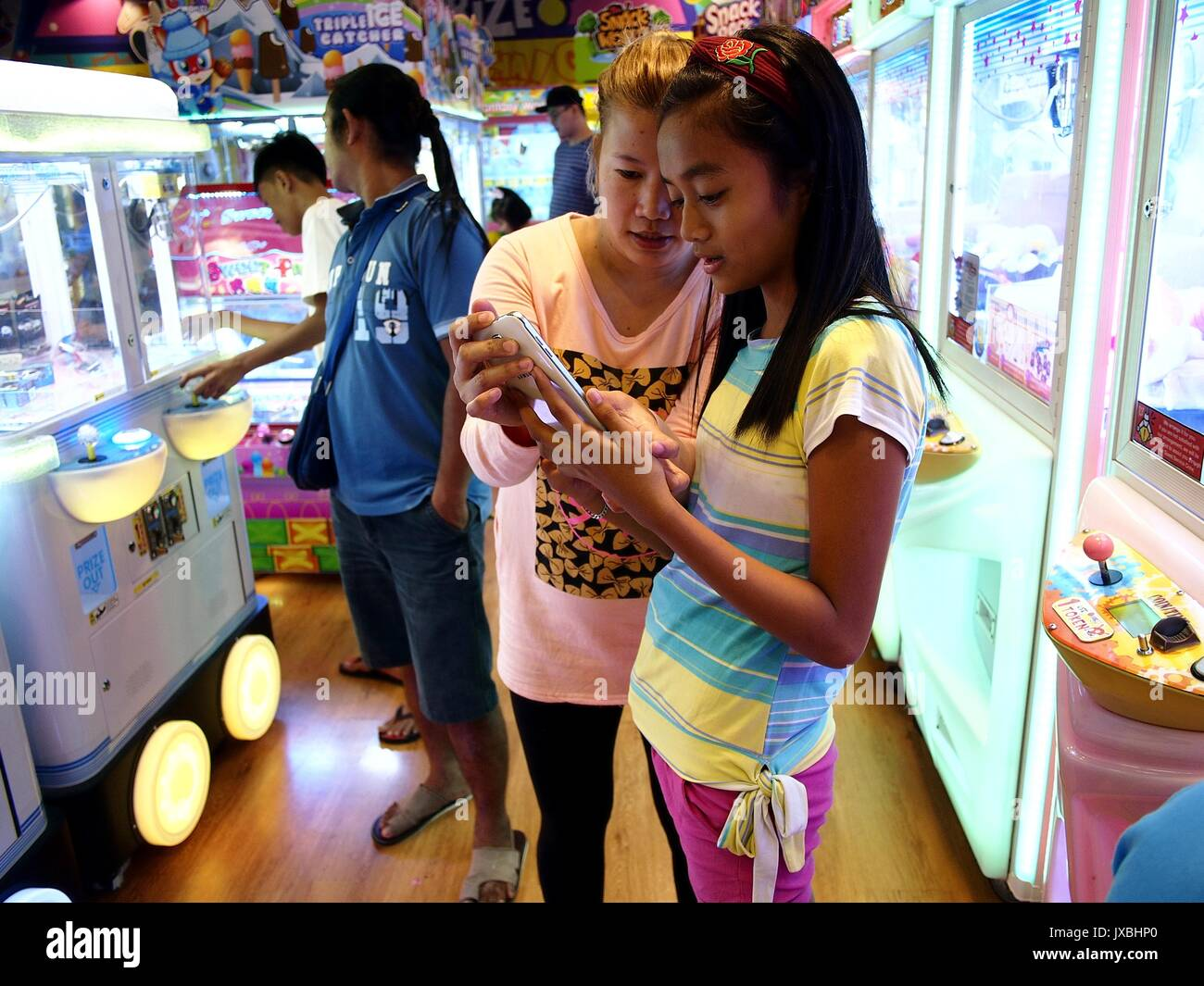ANTIPOLO CITY, PHILIPPINES - AUGUST 13, 2017: Customers enjoy the different attractions inside an amusement arcade. - Stock Image