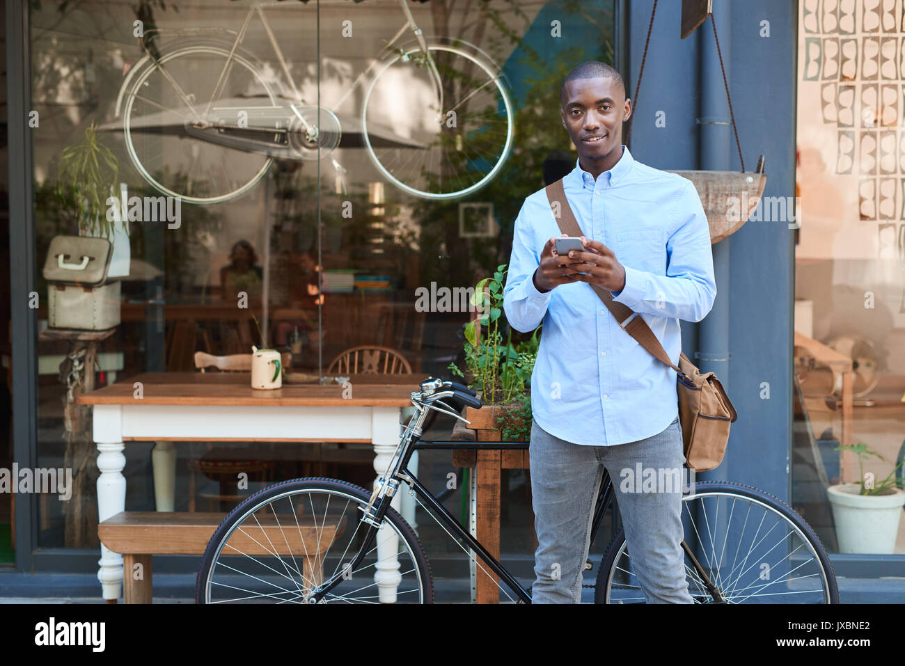 Smiling young man standing in the street reading text messages - Stock Image