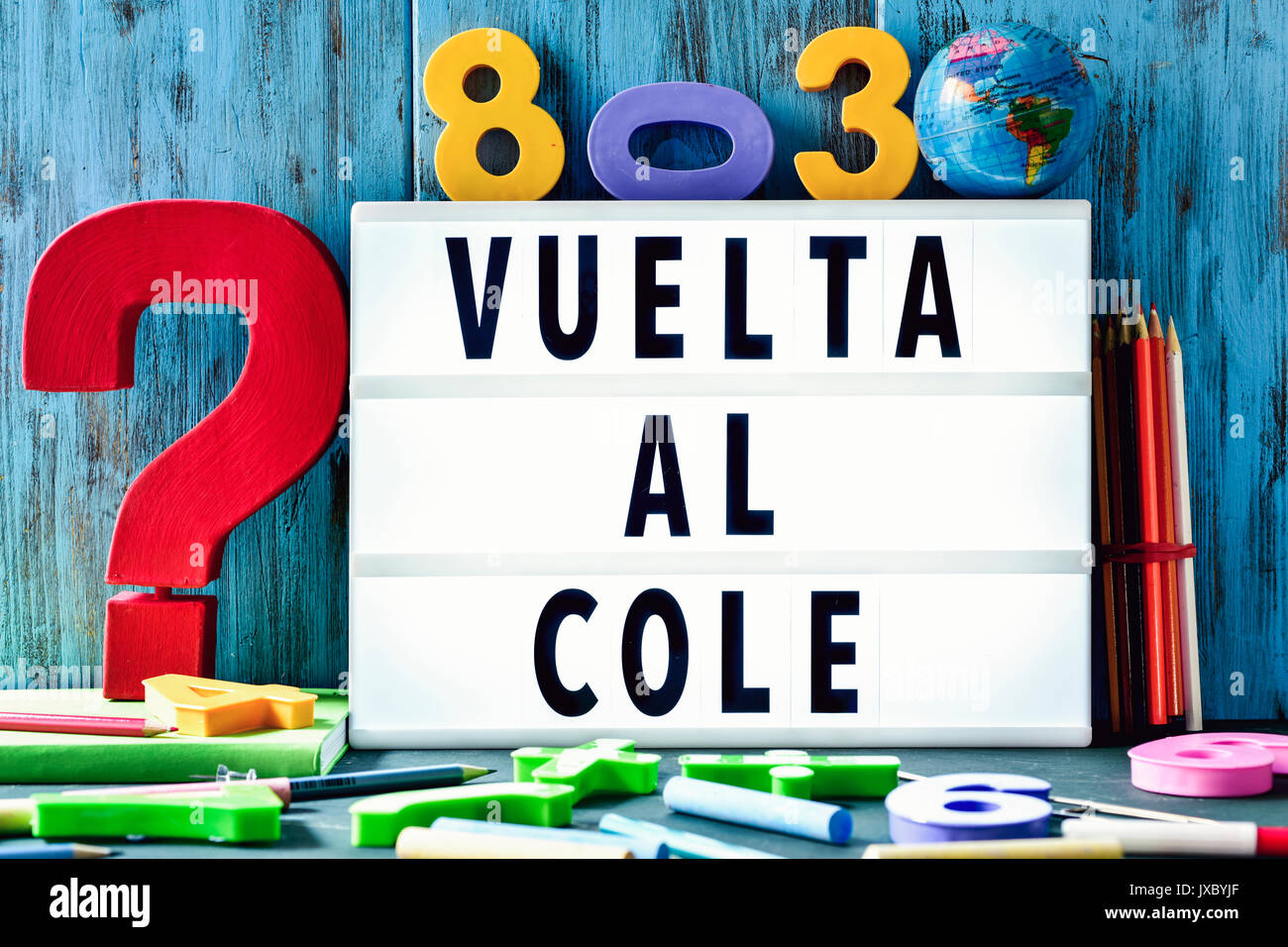 the text vuelta al cole, back to school in spanish, in a lightbox placed against a rustic wooden background, surrounded by three-dimensional numbers a - Stock Image