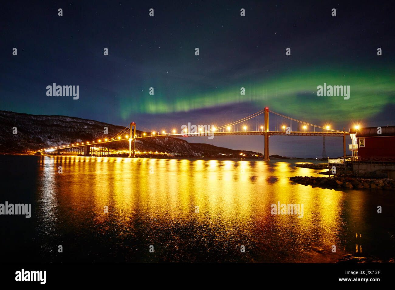 Norther lights above illuminated bridge - Stock Image