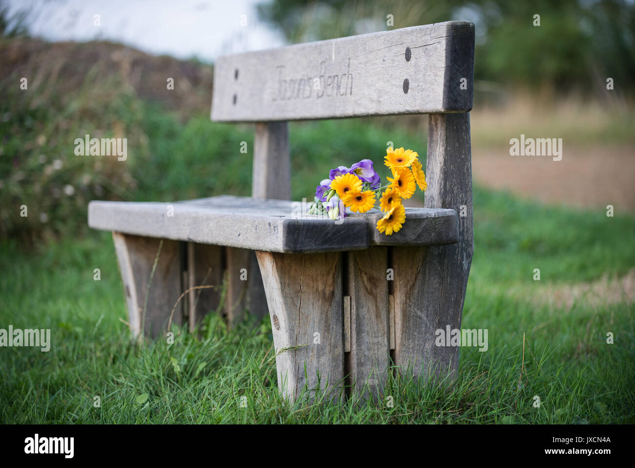 Rustic wooden Memorial bench with flowers at a Natural Burial Ground. Warwickshire, England. United Kingdom. - Stock Image