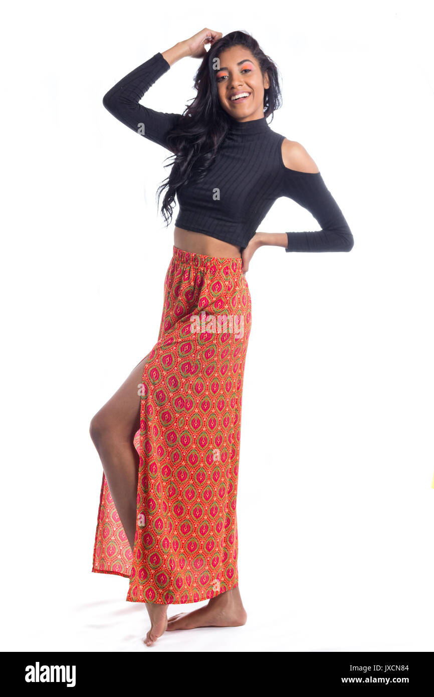 Friendly woman is posing for the photo. Full length body of brazilian girl, mixed ethnicity, wearing black top and long orange skirt. Standing. - Stock Image