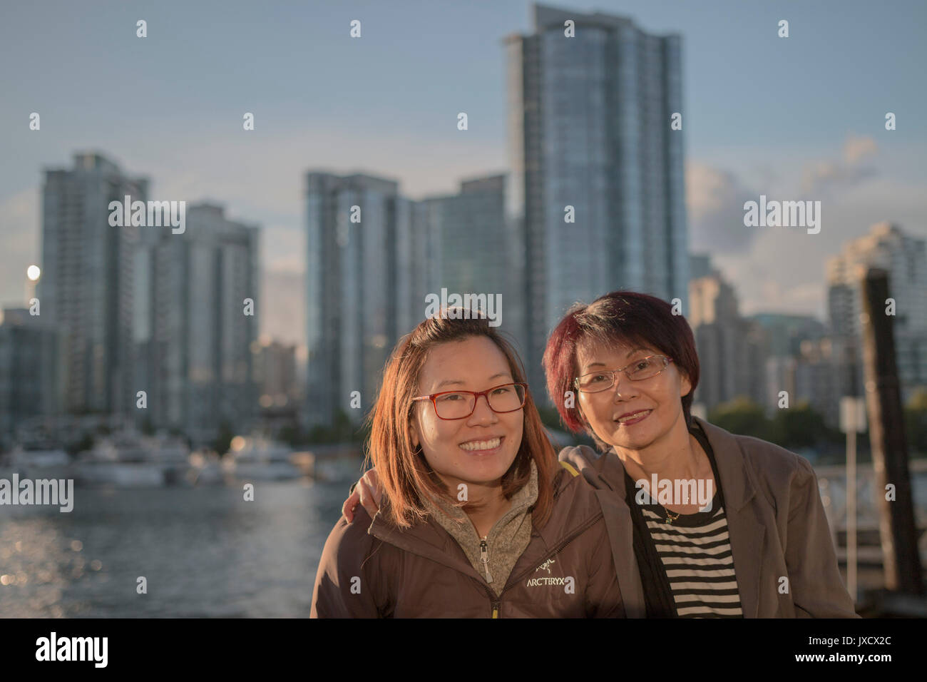 mother and daughter enjoying themselves together with a backdrop of city and sea. - Stock Image