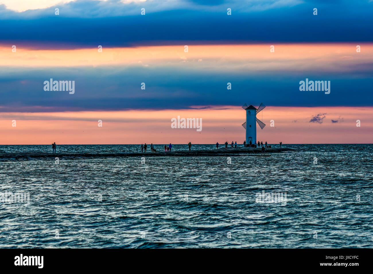 Windmill in Swinoujscie by the Baltic sea by sunset with pink and blue color. Stock Photo