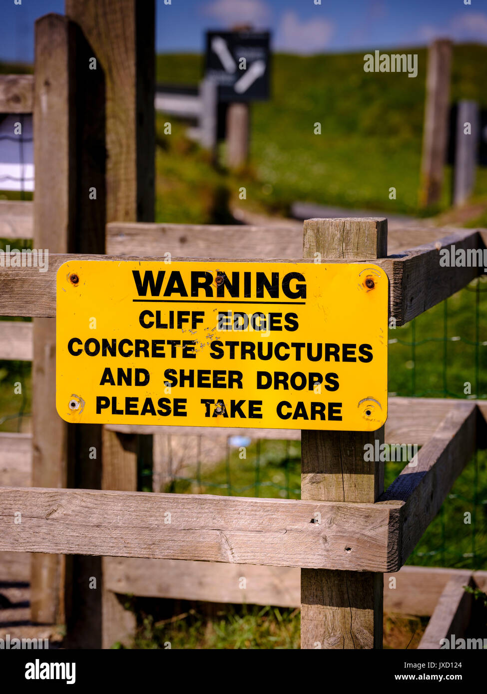 A sign warning of cliff edges, concrete structures and sheer drops, please take care sign at the Needles, Isle of Wight. - Stock Image
