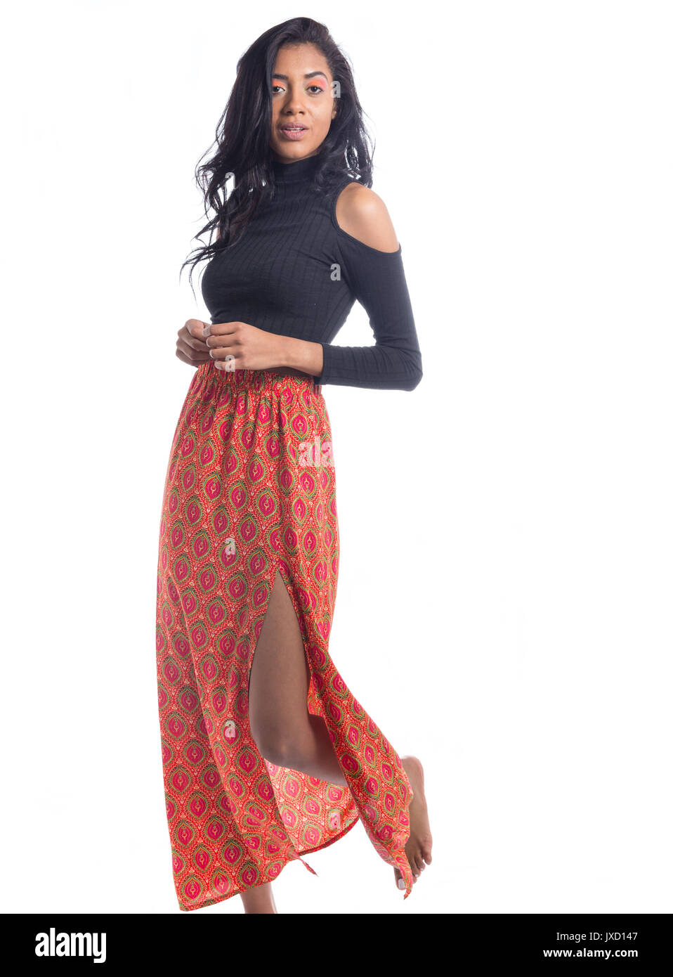 Pretty woman moving with grace. She is beautiful. Full length body of brazilian girl, mixed ethnicity, wearing black top and long orange skirt. Standi - Stock Image
