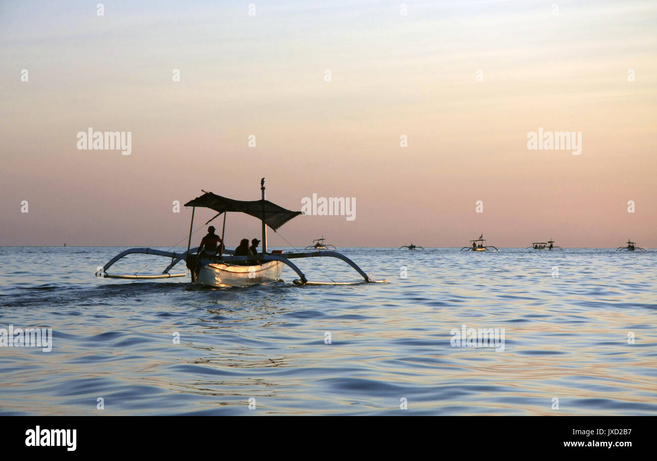 Early morning sunrise at Lovina Beach in Bali, Indonesia with tradtional dolphin watching boats (Jukung) on the horizon - Stock Image