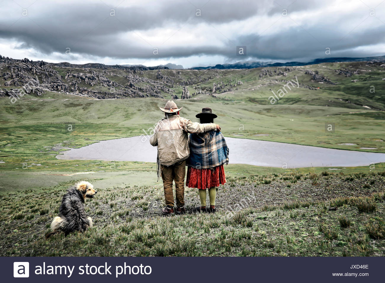 Ayamara indigenous woman and man shepherding at Peruvian highlands with a dog Stock Photo