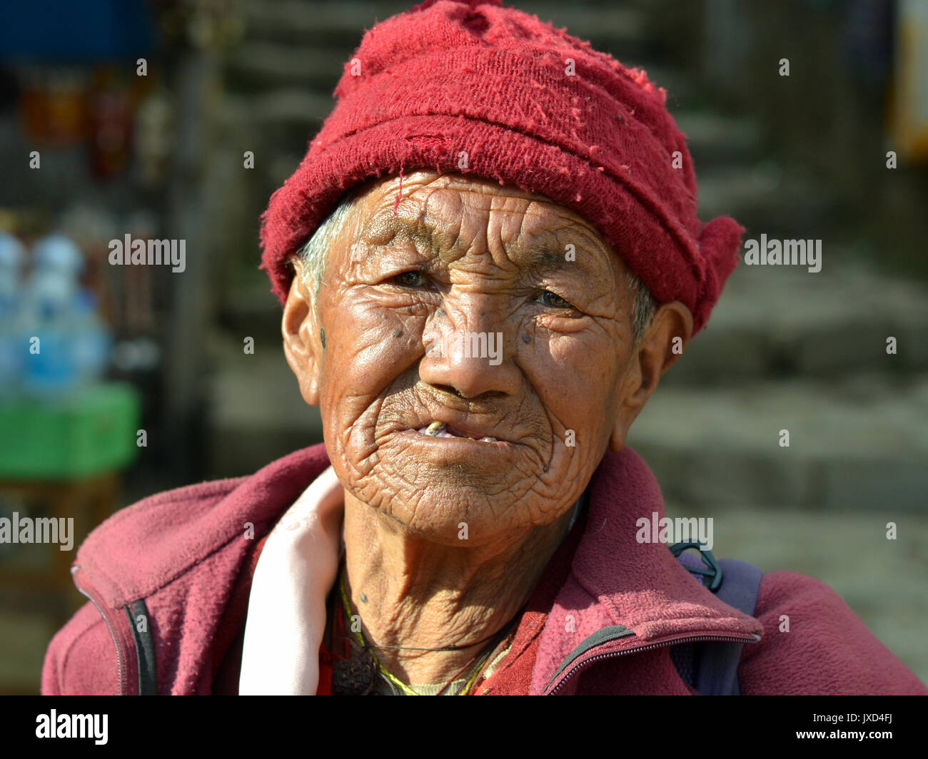 Closeup street portrait (outdoor headshot, full-face view) of an old Tibetan Buddhist nun from the Himalayas; Namche - Stock Image
