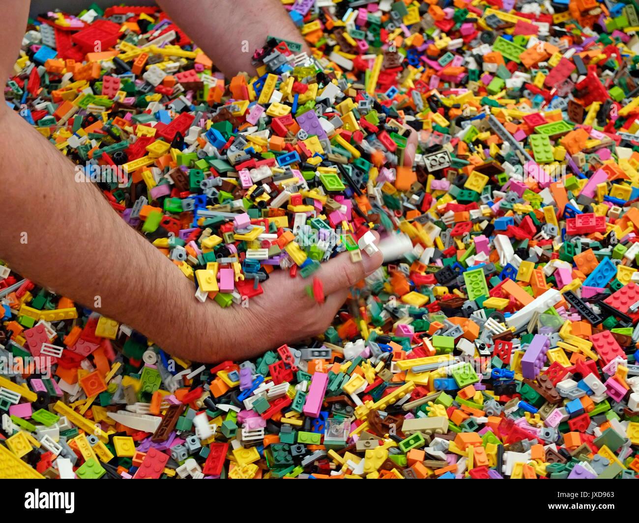 10.08.2017, Legoland Günzburg in Bayern, Ein Besucher greift in die große Schütte mit den bunten Legosteinen. (Modelreleased) Stock Photo