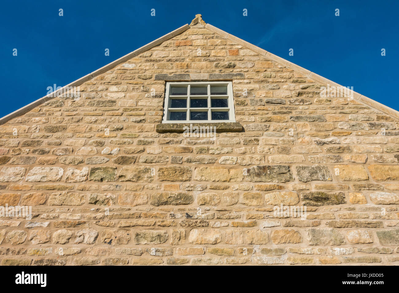 The gable end wall of a barn conversion against a vivid blue sky, Langtoft, near Peterborough, Lincolnvshire, England, UK. - Stock Image