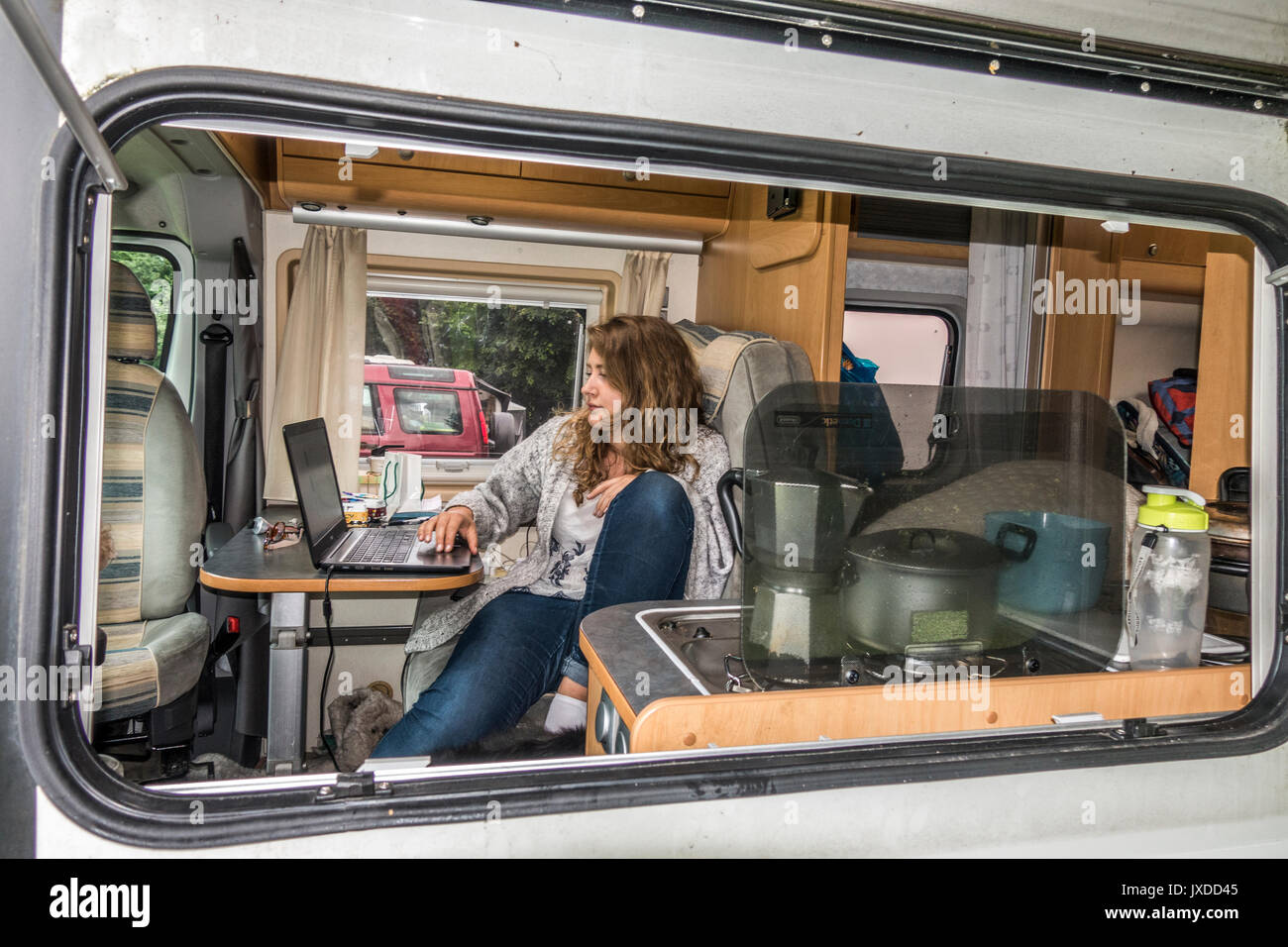 A pretty young woman in a motorhome on a campsite, sitting at her laptop computer. Lydford, Devon, England, UK. - Stock Image
