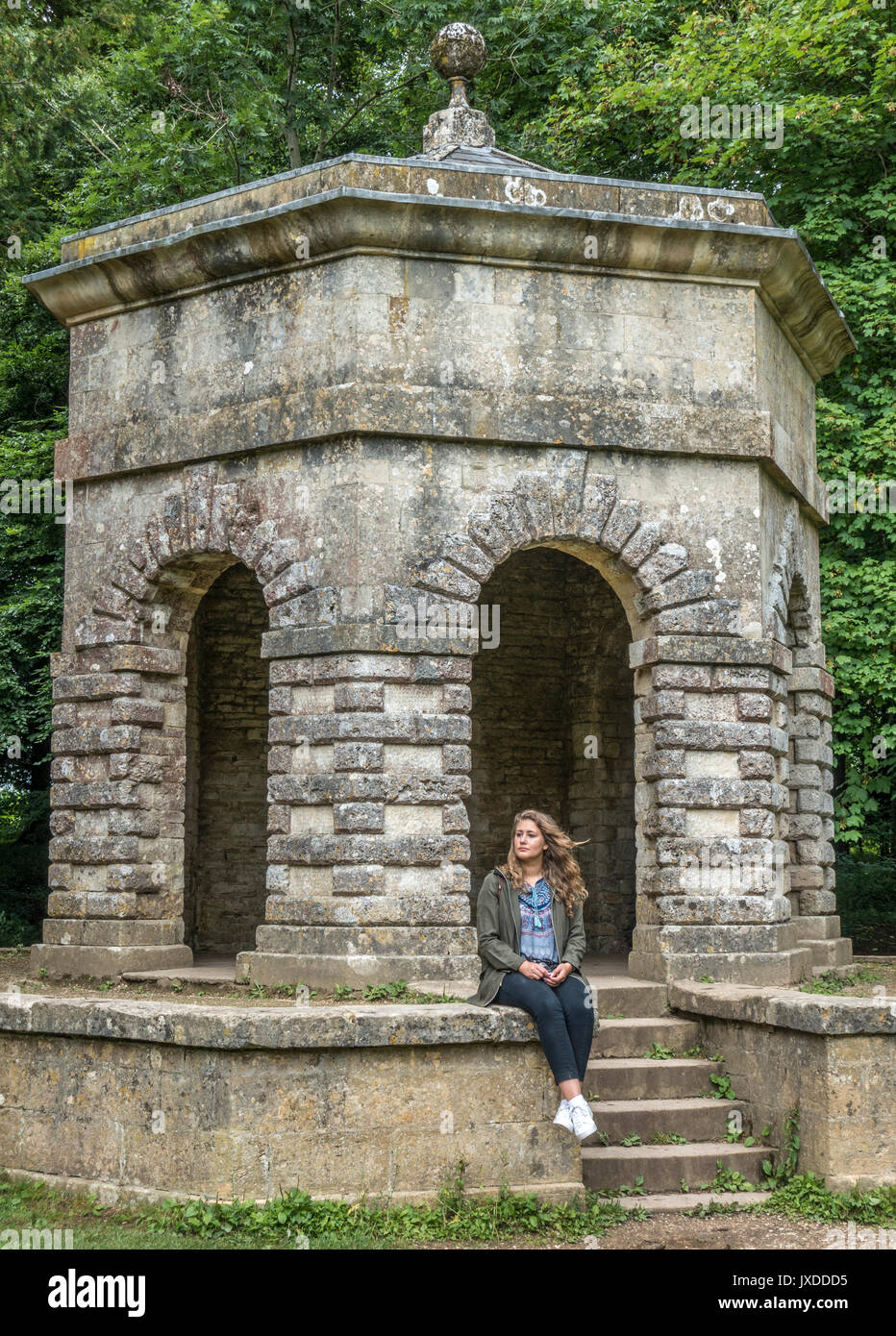 Pretty young woman sitting on The Hexagon Folly in Cirencester Park Gardens, on the Bathurst Estate, Cirencester, Gloucestershire, England, UK. - Stock Image