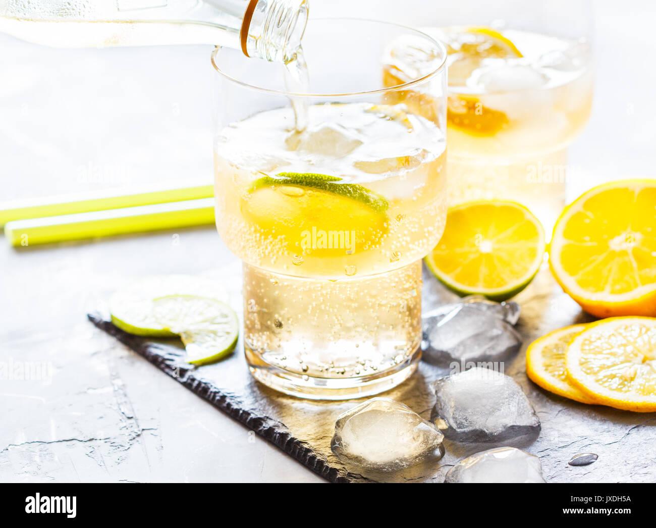 Homemade citrus lemonade in glasses with ice on slate. - Stock Image