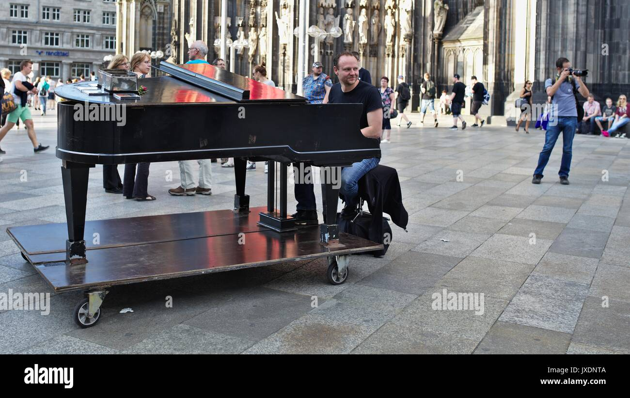 Man playing on grand piano in pedestrian zone in front of Cologne Cathedral main entrance Stock Photo