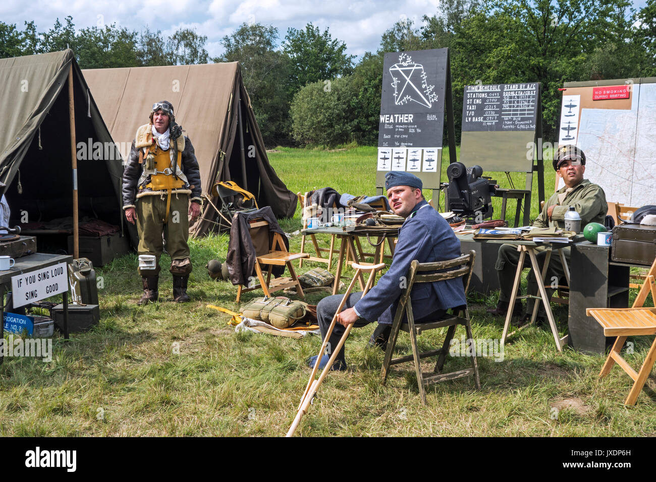 Re-enactors in World War Two battle dresses posing in military re-enactment field camp at WW2 militaria fair Stock Photo