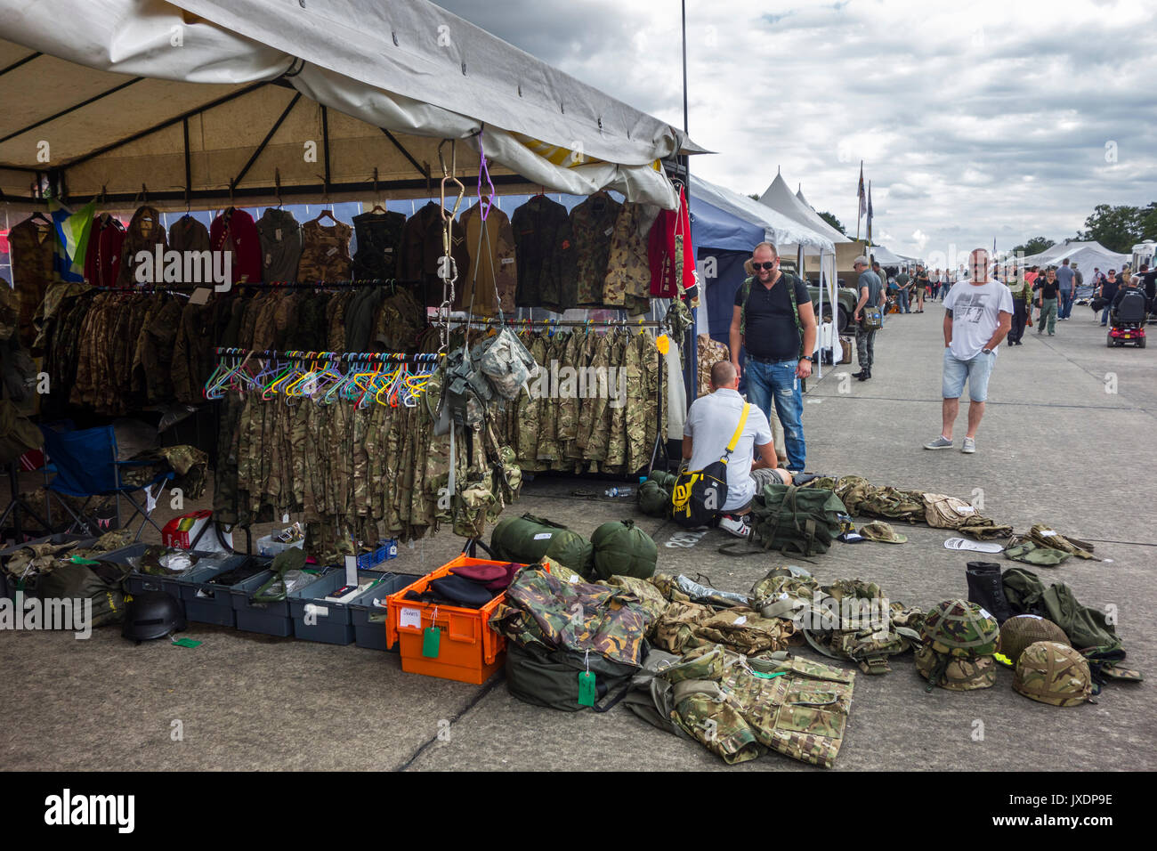 Military uniforms and battle dresses for sale in booth at militaria fair - Stock Image