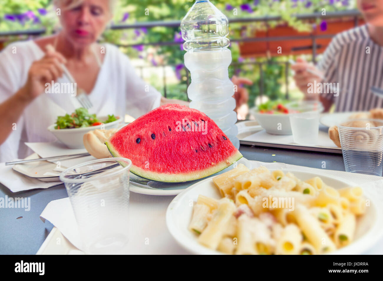 Modern mom and young daughter eating lunch sitting at the table in a water park on summertime. Concept of beautiful people having fun in summertime - Stock Image