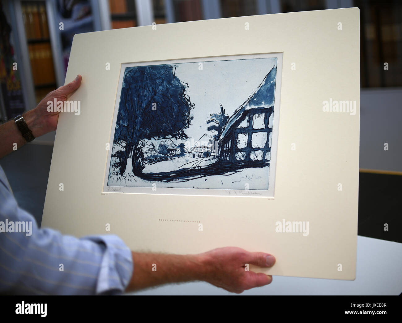Berlin, Germany. 15th Aug, 2017. The deputy director of the Kupferstichkabinett Berlin (Museum of Prints and Drawings), Holm Bevers, holds the etching 'Fehmarnhäuser mit großem Baum' (1908) (lit. Fehmarn houses with big tree) by artist Ernst Ludwig Kirchner in his hands in Berlin, Germany, 15 August 2017. Now, the Prussian Cultural Heritage Foundation bought back the blue test print of an etching after the return to the heirs of the Jewish collector Eugen Moritz Buchtal. Photo: Britta Pedersen/dpa-Zentralbild/dpa/Alamy Live News - Stock Image