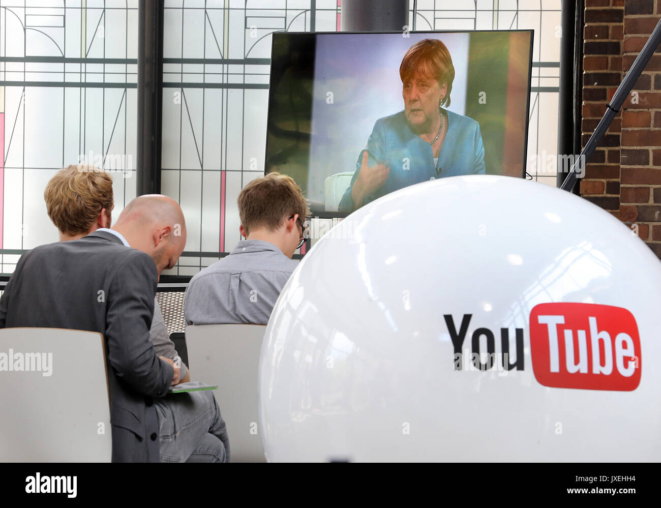 Berlin, Germany. 16th Aug, 2017. People watch from an adjoining room as German Chancellor Angela Merkel is interviewed by Youtubers and the online community in a livestream in Berlin, Germany, 16 August 2017. Photo: Wolfgang Kumm/dpa/Alamy Live News - Stock Image