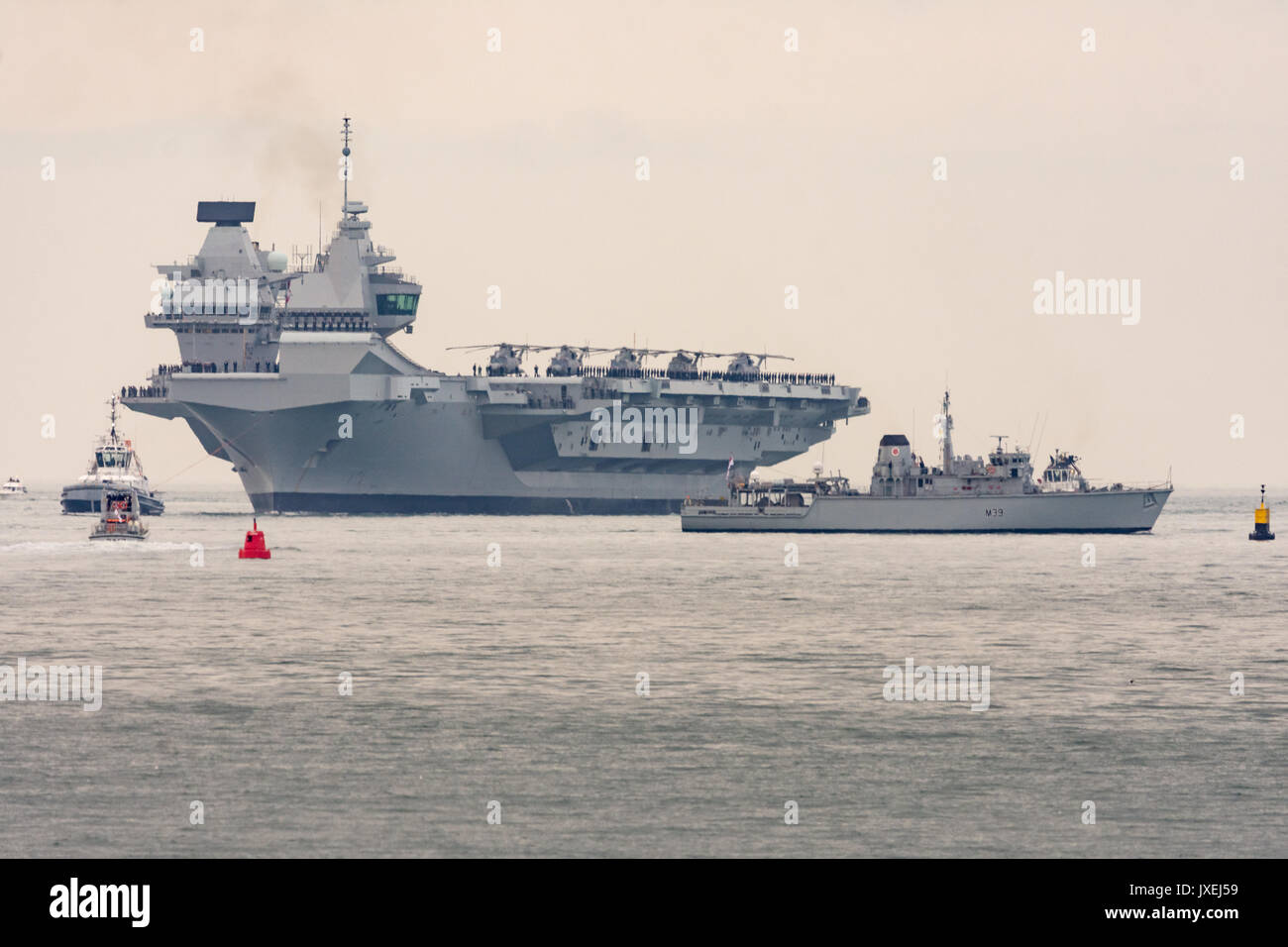 Portsmouth, UK. 16th Aug, 2017. The carrier HMS Queen Elizabeth towers over HMS Hurworth Credit: Vernon Nash/Alamy Live News - Stock Image