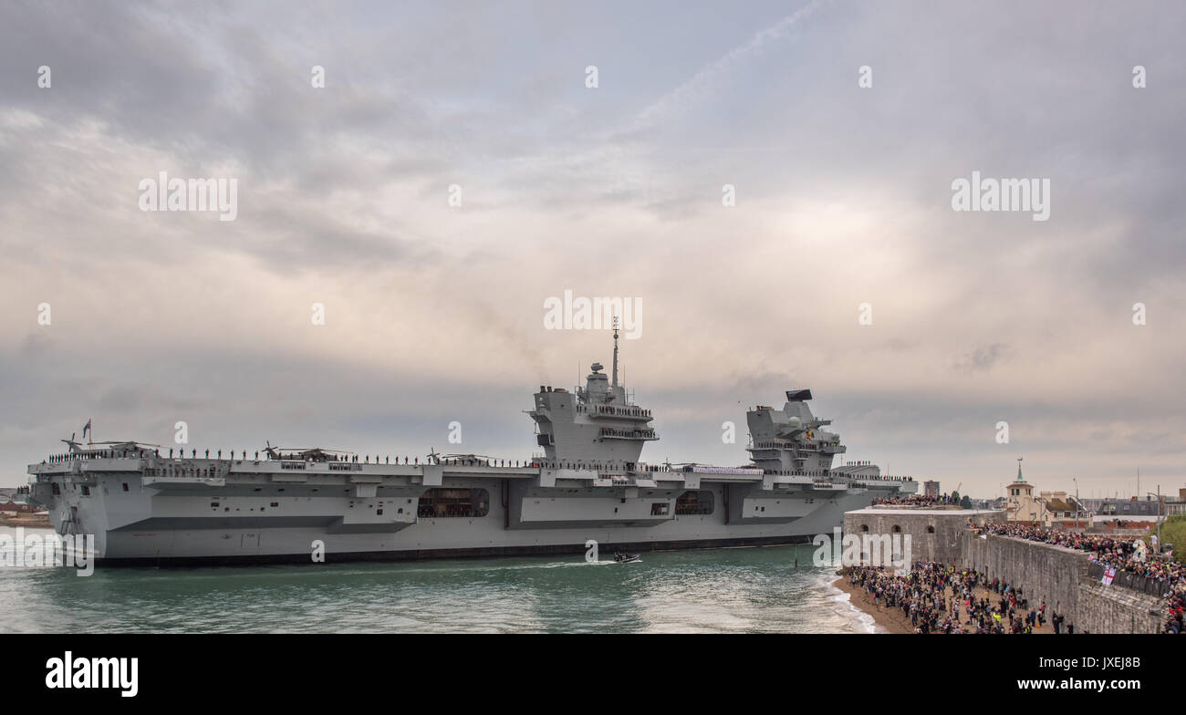 Portsmouth, UK. 16th Aug, 2017. New aircraft carrier HMS Queen Elizabeth dwarfs the harbour entrance Credit: Vernon Nash/Alamy Live News - Stock Image