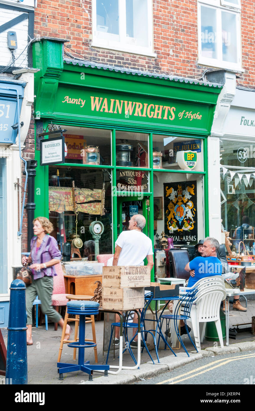 People sitting outside Aunty Wainwrights of Hythe antiques and collectables shop. - Stock Image